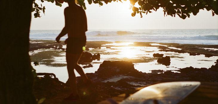 Sun sets behind a surfer