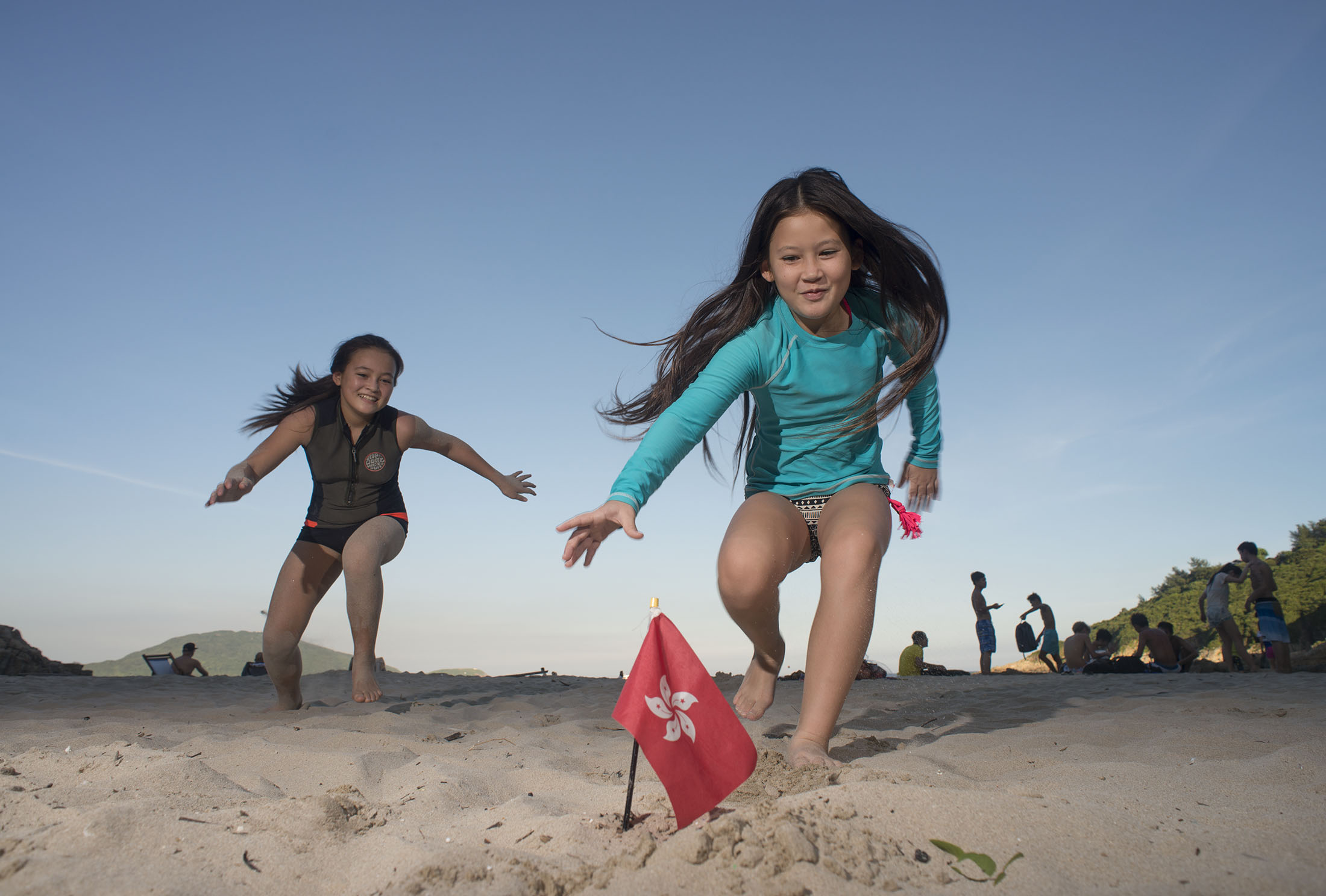 Two girls play beach games chase the flag